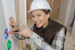 Glücklicher weiblicher Erbauer mit Schraubenzieherfestlegungssockel zuhause stockbilder