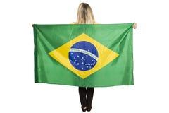 Glücklicher weiblicher Fan mit der brasilianischen Flagge, die einen Fußball hält stockbild