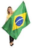Glücklicher weiblicher Fan mit der brasilianischen Flagge, die einen Fußball hält stockfoto