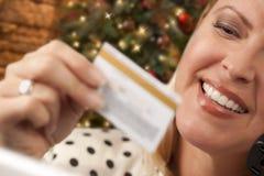 Glücklicher weiblicher Käufer, der Kreditkarte durch Weihnachtsbaum hält Stockfotos