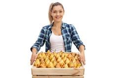 Glücklicher weiblicher Landwirt, der eine Kiste voll von den Birnen hält Stockbild
