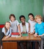 Glücklicher weiblicher Schreibtisch Professor-With Students At Lizenzfreie Stockfotografie