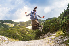 Glücklicher weiblicher Wanderer, der in Berge an einem schönen sonnigen Tag springt stockbild