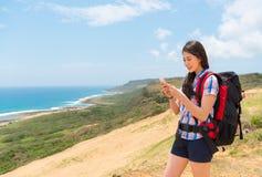 Glücklicher weiblicher Wanderer, der das intelligente Mobiltelefon verwendet Lizenzfreies Stockfoto