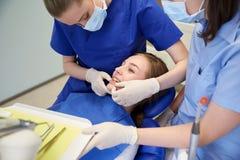 Glücklicher weiblicher Zahnarzt mit geduldigem Mädchen an der Klinik stockfotos
