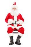 Glücklicher Weihnachtsmann, der auf einem Holzstuhl sitzt Stockfotografie