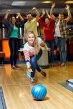 Glücklicher werfender Ball der jungen Frau im Bowlingspielverein Stockfotografie