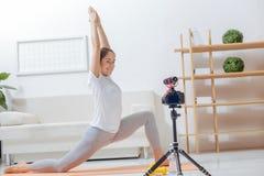 Glücklicher Yogalehrer, der ihre Übungen für ein Videoblog und ein Lächeln notiert Stockbilder