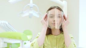Glücklicher Zahnarzt, der oben Schutzmaske in der zahnmedizinischen Klinik kleidet Junger Doktor stock footage