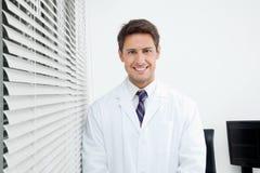 Glücklicher Zahnarzt Standing In Clinic Stockfoto