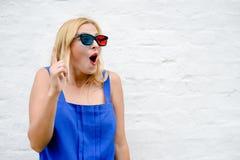 Glücklicher Zeigeaufpassender Film des fingers des schönen blonden Mädchens mit Gläsern 3D, aufregendes Schreien Porträtnahaufnah Stockfotografie