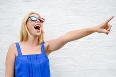 Glücklicher Zeigeaufpassender Film des fingers des schönen blonden Mädchens mit Gläsern 3D, aufregendes Schreien Porträtnahaufnah Lizenzfreie Stockfotos