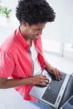 Glücklicher zufälliger Geschäftsmann unter Verwendung des Laptops Lizenzfreies Stockbild