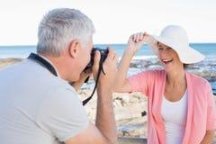 Glücklicher zufälliger Mann, der ein Foto des Partners durch das Meer macht Stockfotos