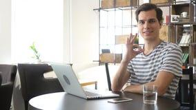 Glücklicher zufälliger Mann, der o.k. im Büro, lächelnd zeigt stockfoto