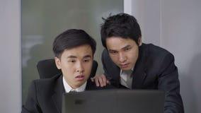 Glücklicher zwei Geschäftsmann, der eine Laptop-Computer zum erfolgreichen Funktionsprojekt verwendet stock footage