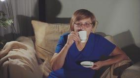 Glückliches älteres Frauenlächeln, sitzend in trinkendem Tee des Lehnsessels stock footage
