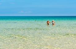 Glückliches älteres Paar genießt einen romantischen Weg im haarscharfen Wasser auf dem Strand Sans Vito Lo Capo Stockbild