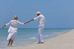 Glückliches älteres Paar-Tanzen auf einem tropischen Strand lizenzfreie stockfotografie