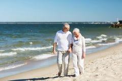 Glückliches älteres Paarhändchenhalten auf Sommerstrand stockbilder