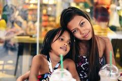Glückliches Abbinden von zwei Schwestern in einem Café eiskalte Erschütterung trinkend lizenzfreies stockfoto