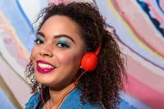 Glückliches afrikanisches Frauenanhörungslied durch Kopfhörer Stockbilder