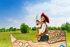 Glückliches afrikanisches Mädchen als Pirat mit Hut und Klinge Stockbilder