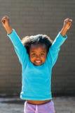 Glückliches afrikanisches Mädchen, das hoch Arme anhebt Stockfotos