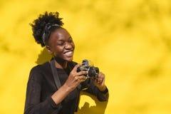 Glückliches afrikanisches Mädchen mit der Digitalkamera im Freien stockfoto