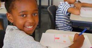 Gl?ckliches afro-amerikanisches Schulm?dchen, das in der Schule am Schreibtisch in einem Klassenzimmer 4k studiert stock footage