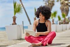 Glückliches afroes-amerikanisch Frauensitzen kreuzte Beine unter Verwendung der Tablette Lizenzfreies Stockfoto