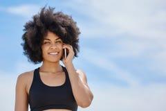 Glückliches afroes-amerikanisch Mädchen, das auf Mobile spricht Lizenzfreie Stockfotografie