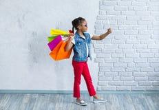 Glückliches Afromädchen mit Einkaufstaschen Stockfoto