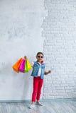 Glückliches Afromädchen mit Einkaufstaschen Stockfotos