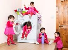 Glückliches aktives kleines Kind, das Waschmaschine verwendet Lizenzfreie Stockbilder