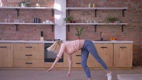 Glückliches aktives Mädchen, das gymnastischen leichten Schlag in der Zeitlupe an der Küche tut stock video