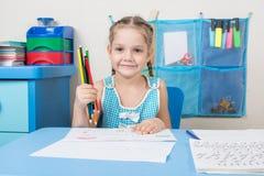 Glückliches altes Fünfjahresmädchen hob einen farbigen Bleistift auf und untersuchte den Rahmen Stockfotos