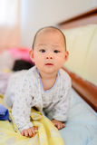 Glückliches asiatisches Baby auf Bett Stockbilder