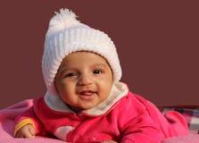 Glückliches asiatisches Baby in der weißen Winterschutzkappe Stockbild