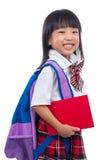 Glückliches asiatisches chinesisches kleines Mädchen mit Schultasche und Buch Lizenzfreie Stockfotografie