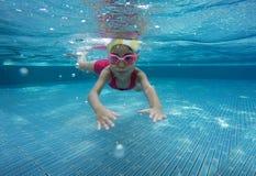 Glückliches asiatisches Kind, das unter Wasser im Sommer schwimmt lizenzfreies stockbild