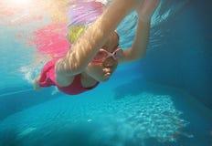 Glückliches asiatisches Kind, das unter Wasser im Sommer schwimmt Lizenzfreies Stockfoto