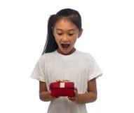 Glückliches asiatisches Kindermädchen mit roter Geschenkbox lizenzfreies stockfoto