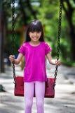 Glückliches asiatisches kleines Mädchen, das auf Schwingen lächelt stockfotos
