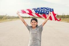 Glückliches asiatisches kleines Mädchen mit amerikanischer Flagge USA feiern Juli 4. stockfotografie