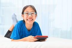 Glückliches asiatisches Mädchen, das einen ebook Leser hält und an Kamera w lächelt stockbilder