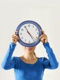 Glückliches asiatisches Mädchen, das große blaue Uhr hält Stockbild