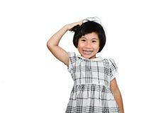 Glückliches asiatisches Mädchen, das ihren Kopf verkratzt Stockfoto