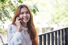Glückliches asiatisches Mädchen, das mit Handyfront des hohen buildin spricht stockbild