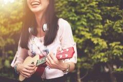 Glückliches asiatisches Mädchen, das Ukulele an im Freien spielt stockfotos
